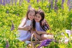 俄罗斯,喀山- 2019 6月7日,两个女婴在花中的一个电话做selfie在一个领域在一好日子 夏天的概念 免版税库存照片