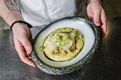 俄罗斯,圣彼德堡,03 17 2019厨师准备大比目鱼在芹菜下在餐馆厨房里 免版税库存照片