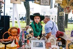 俄罗斯,城市莫斯科- 2014年9月6日:一个帽子有paly的和绿色围巾的年轻美女 妇女卖在a的古董 图库摄影