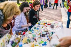 俄罗斯,城市莫斯科- 2014年9月6日:孩子在街道上画 年轻少年坐在桌和凹道上与刷子 库存照片