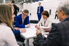 俄罗斯,城市莫斯科- 2017年12月18日:男人和妇女谴责项目在会议上 起始的商人是 库存照片