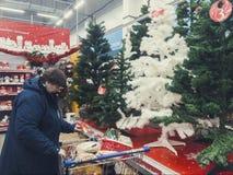 俄罗斯,摩尔曼斯克11月10日2018年:人们在超级市场选择圣诞树的圣诞节玩具 免版税库存照片