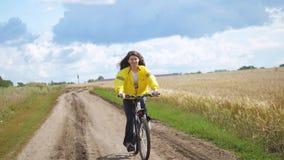 俄罗斯,新西伯利亚, 20威严2017年 某人与儿童骑马自行车的愉快的家庭在夏时的麦田 股票视频