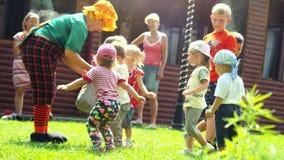 俄罗斯,新西伯利亚, 2016年7月23日 使用与明亮的服装的设计卡通者的快乐的孩子室外在草在 影视素材