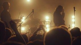 俄罗斯,新西伯利亚, 2016年7月14日 在摇滚乐音乐会的爱好者在夜总会 免版税库存图片