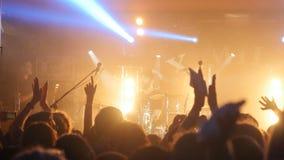 俄罗斯,新西伯利亚, 2016年7月14日 摇他们的手的爱好者拥挤集会在夜总会的摇滚乐音乐会 免版税图库摄影