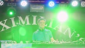 俄罗斯,新西伯利亚, 2015年9月11日 棍打,迪斯科愉快的人人群的DJ使用的和混合的音乐慢动作的 股票录像
