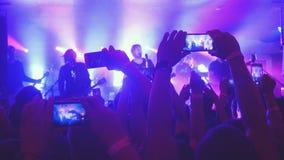 俄罗斯,新西伯利亚, 2016年7月14日 爱好者递录音录影和与巧妙的电话的采取图片在音乐音乐会 免版税库存照片