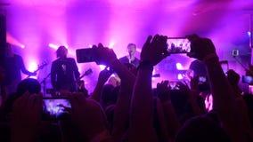 俄罗斯,新西伯利亚, 2016年7月14日 爱好者递录音录影和与巧妙的电话的采取图片在音乐音乐会 免版税图库摄影