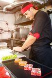 俄罗斯,梁赞- 12 11 2018 - 微笑的亚裔厨师用在厨房的寿司 免版税图库摄影
