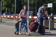 俄罗斯,莫斯科,伏努科沃, 2018年6月27日,有旅行在街道上的两个孩子的一个家庭在夏天,社论 库存照片