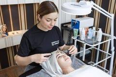 俄罗斯,莫斯科,2019年5月18日 患者由审美诊所的美容师接受电面部按摩 库存照片