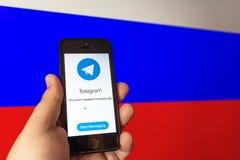 俄罗斯,莫斯科- 2018年4月16日:电报在智能手机的信使应用在俄国旗子背景的人手上 库存图片