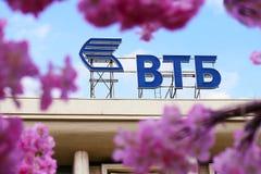 俄罗斯,莫斯科- 2018年4月30日 VTB通过一棵装饰樱桃树的花看的银行商标在莫斯科街道上的 免版税库存图片