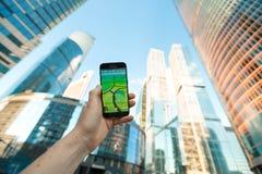 俄罗斯,莫斯科- 8月24 :2016年有Pokemon的智能手机去应用 在摩天大楼背景  被增添的 库存照片