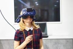 俄罗斯,莫斯科- 2019 A女孩神色4月,04,到一件虚拟现实盔甲里 库存图片