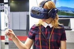 俄罗斯,莫斯科- 2019 A女孩神色4月,04,到一件虚拟现实盔甲里 图库摄影
