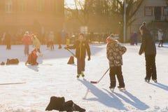 俄罗斯,萨拉托夫, 2018年1月13日,计时15 00 滑冰在滑冰场和打曲棍球的人们在体育场内 库存照片