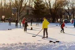 俄罗斯,萨拉托夫, 2018年1月13日,计时15 00 滑冰在滑冰场和打曲棍球的人们在体育场内 库存图片