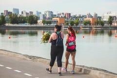 俄罗斯,顿河畔罗斯托夫6月03日厚实2018两个的女孩-和运动走沿体育衣裳的湖,在跑步以后 免版税库存照片