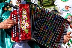 俄罗斯,马格尼托哥尔斯克,- 2019年6月,15日 全国衣裳的一个人播放手风琴-图拉口琴 在的Sabantuy的游行- 免版税库存照片