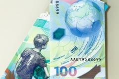 俄罗斯- 2018年6月:纪念世界杯足球赛2018 100卢布钞票, 25磨擦硬币  免版税库存图片