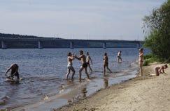 俄罗斯- Berezniki 7月18日:青年人跳进河在日落 库存图片