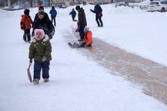 俄罗斯Berezniki 2018年2月20日:孩子和成人在冬天滑下来城市广场的冰冷的地狱 33c 1月横向俄国温度ural冬天 库存图片