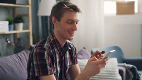 俊男付与信用卡和智能手机触摸屏然后微笑的享用的电子付款 影视素材