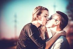 俏丽夫妇亲吻室外在森林里 免版税库存图片