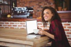 俏丽深色喝咖啡使用膝上型计算机 免版税库存照片