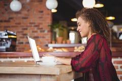 俏丽深色喝咖啡使用膝上型计算机 免版税库存图片