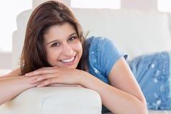 俏丽深色微笑对在长沙发的照相机 免版税图库摄影
