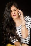 俏丽深色谈话在她的有她的眼睛的手机关闭了 免版税库存图片