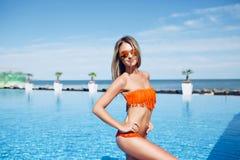 俏丽的亭亭玉立的白肤金发的女孩在太阳的水池附近站立 她穿橙色比基尼泳装 她是摆在和微笑对 库存图片