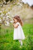 俏丽的儿童女孩在庭院里嗅到花 库存图片