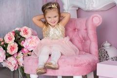 俏丽的儿童女孩坐桃红色椅子 免版税图库摄影