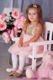 俏丽的儿童女孩坐桃红色椅子 库存图片