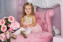 俏丽的儿童女孩坐桃红色椅子 免版税库存照片