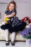 俏丽的儿童女孩拿着两条小狗 免版税库存照片