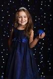 俏丽的儿童女孩拿着蓝色圣诞节球 库存照片