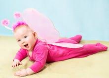 俏丽的儿童女孩,打扮在背景的蝴蝶服装 免版税库存照片