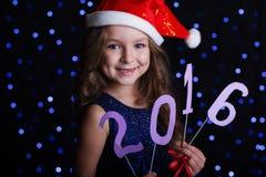 俏丽的圣诞老人女孩与新年日期2016年 免版税库存图片