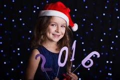 俏丽的圣诞老人女孩与新年日期2016年 库存照片