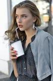 俏丽的在一纸杯外面的女孩饮用的饮料 免版税库存照片
