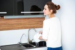 俏丽的在厨房的妇女洗涤的盘后面看法  免版税库存照片