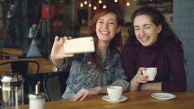 俏丽的在咖啡馆时采取与智能手机的selfie然后观看照片的女孩最好的朋友,当喝咖啡 股票录像