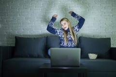 俏丽的在她的膝上型计算机的妇女观看的电影在夜间一部暗室观看的电影和培养手的床上  库存图片