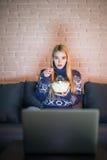 俏丽的在她的膝上型计算机的妇女观看的电影在夜间一部暗室观看的电影的床上 免版税库存图片