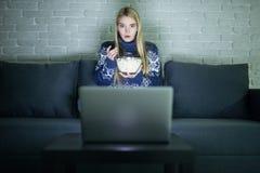 俏丽的在她的膝上型计算机的妇女观看的电影在夜间一部暗室观看的电影的床上 免版税库存照片